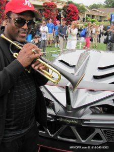 Both trumpet and car are made of carbon fiber. picture inside lamborghini exhibit with Jon Barnes holding trumpet up in front of concept car.